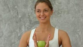 Беспечальная здоровая испанская женщина держа зеленый усмехаться яблока Стоковое фото RF