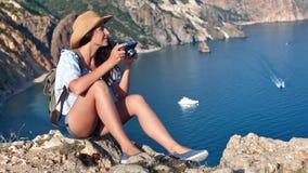 Беспечальная молодая женщина перемещения имея положительную эмоцию фотографируя используя камеру восхищая ландшафт моря сток-видео
