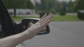 Беспечальная молодая женщина развевая ее рука вне двигая окна автомобиля акции видеоматериалы