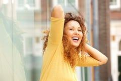 Беспечальная молодая женщина смеясь с руками за главным снаружи стоковые изображения