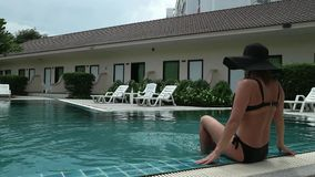 Беспечальная тонкая женщина разматывает и загорает около бассейна в летнем дне акции видеоматериалы