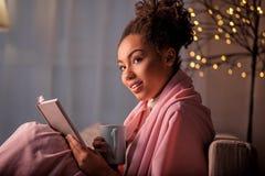 Беспечальное чтение молодой женщины на софе Стоковое Изображение RF