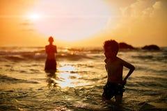 Беспечальные братья стоя в море против ясного неба во время захода солнца Стоковое Изображение RF