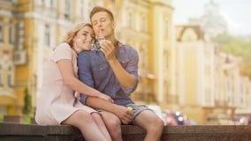 Беспечальные пузыри мыла молодого человека дуя, пары наслаждаясь летом датируют в городе стоковые фото