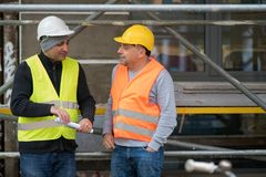 Беспечальный говорить между 2 гражданскими инженерами во время пролома работы на строительной площадке Стоковое Изображение RF