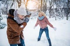 Беспечальный молодой человек и женщина играя снежные комья стоковое изображение rf