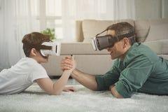 Беспечальный родитель и ребенк состязаясь в армрестлинге с устройствами стоковая фотография