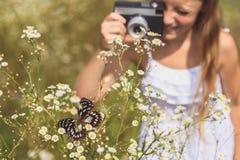 Беспечальная девушка фотографируя тварь на поле Стоковые Изображения