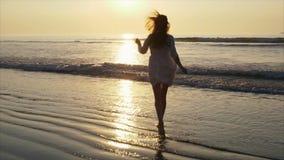 Беспечальная женщина в barefeet бежать к морю во время захода солнца видеоматериал