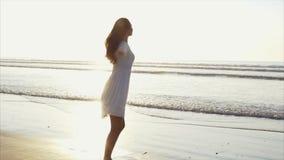 Беспечальная женщина поворачивая и вертясь вокруг на пляже видеоматериал
