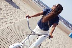 Беспечальная женщина с катанием велосипеда на пляже Стоковые Изображения
