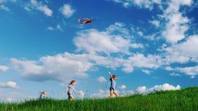 Беспечальная игра детей с змеем Бежать вдоль зеленого холма против голубого неба с белыми облаками детство счастливое сток-видео