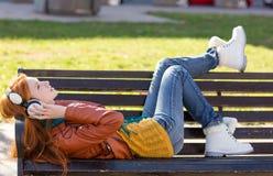 Беспечальная молодая дама лежа на стенде и слушая к музыке Стоковая Фотография