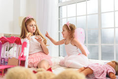 Беспечальные девушки есть торт на кровати Стоковые Изображения