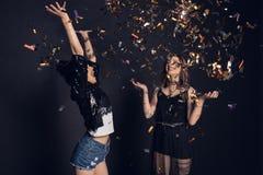 Беспечальные стильные молодые женщины имея потеху с confetti Стоковые Изображения