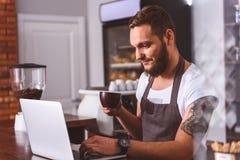 Беспечальный бармен отдыхая в кофейне стоковое фото rf
