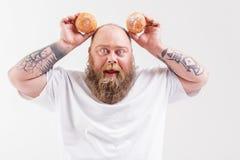 Беспечальный тучный человек играя с donuts Стоковые Фото