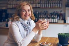 Беспристрастная зрелая женщина наслаждаясь чашкой чаю Стоковые Фотографии RF