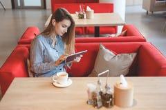 Беспристрастное изображение молодой женщины используя планшет в кафе Стоковое Фото