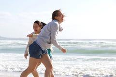 Беспристрастные женщины смеясь над на пляже Стоковое Фото