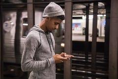 Беспристрастный портрет детеныша, чернокожего человека используя его телефон в новом y Стоковые Изображения RF