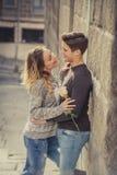Беспристрастный портрет красивых европейских пар с поднял в влюбленность целуя на переулке улицы празднуя день валентинок Стоковые Фотографии RF