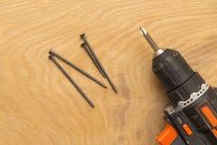 Беспроволочная отвертка и само-выстукивая винты на деревянной предпосылке, теме работы ремонта, конца-вверх стоковое фото