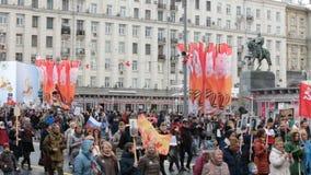 Бессмертное шествие полка в дне победы - тысячах людей маршируя вдоль улицы Tverskaya к красной площади с флагами акции видеоматериалы