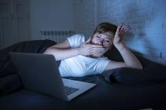 Бессонная молодого красивого интернета пристрастившийся и утомленная женщина работая на компьтер-книжке в кровати поздно на ноче стоковое изображение rf