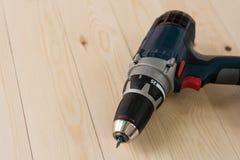 Бесшнуровые сверло и отвертка с перезаряжаемые батареей на деревянном столе с космосом экземпляра Стоковая Фотография RF