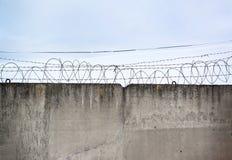 Бетонная стена, против фона колючей проволоки, концепция стоковая фотография rf