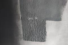 Бетонная стена частично покрашенная в сером цвете с роликом краски Покрасьте текстуру в бортовом солнечном свете стоковое изображение