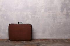 Бетонные стены и деревянный пол с чемоданом Стоковые Изображения