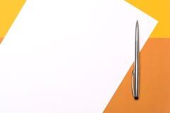 Белая бумага и ручка на предпосылке желтого коричневого цвета стоковые фотографии rf