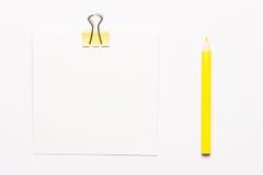 Белая бумага примечания и желтые paperclips Стоковые Изображения