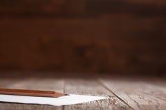 Белая бумага при карандаш кладя на деревянный стол горизонтальный Стоковые Изображения RF