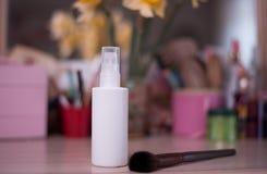 Белая бутылка для косметики с нерезкостью щетки предпосылка на животиках стоковые фото