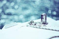 Белая веревочка зачаливания связанная вокруг стального анкера на шлюпке Стоковые Изображения