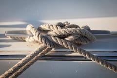 Белая веревочка зачаливания связанная вокруг стального анкера на шлюпке или корабле Стоковое Фото