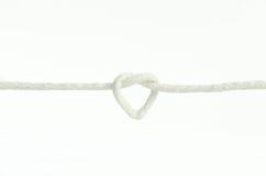 белая веревочка связанная в изолированном узле влюбленности формы сердца   Стоковые Фото