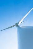 Белая ветротурбина производя электричество на голубом небе стоковые фотографии rf