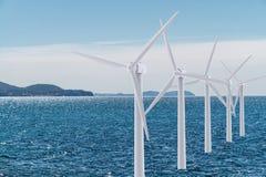 Белая ветротурбина производя электричество на море стоковое фото rf