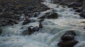 Белая вода каскадируя отмелый поток пропуская между серыми утесами в сибирской гористой местности горы видеоматериал