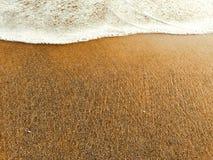 Белая волна пены на желтом песчаном пляже, полная вода, теплое море и песок приставают к берегу Стоковые Изображения RF
