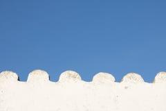 Белая волнистая пустая стена в голубом небе с космосом экземпляра Стоковые Фото