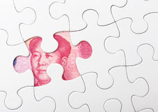 Белая головоломка и китайская банкнота Стоковая Фотография