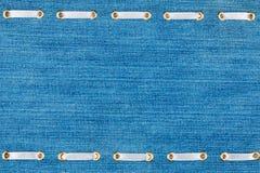 Белая лента сатинировки введенная в кольца золота на голубой джинсовой ткани Стоковые Фотографии RF