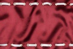 Белая лента сатинировки введенная в кольца золота на красном шелке Стоковые Фотографии RF