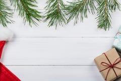 Белая деревянная предпосылка украсила ветви и подарочные коробки сосны Стоковые Изображения