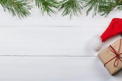 Белая деревянная предпосылка украсила зеленые ветви ` s сосны Стоковые Фотографии RF